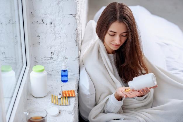 Mulher derramando medicação, comprimidos e cápsulas na mão Foto Premium