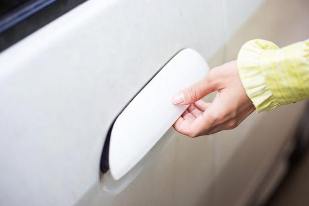 Mulher desbloquear e abrir a porta do carro branco Foto Premium