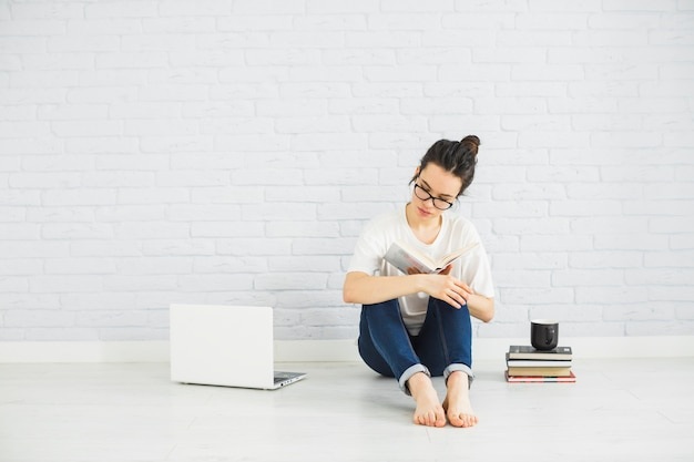Mulher descalça lendo perto de laptop Foto gratuita