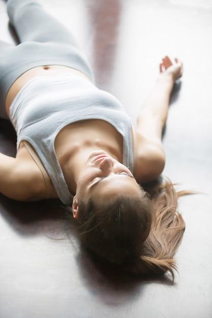 Mulher descansando depois de praticar yoga em casa Foto gratuita