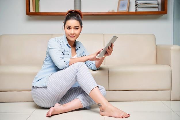 Mulher descansando em casa com tablet Foto gratuita