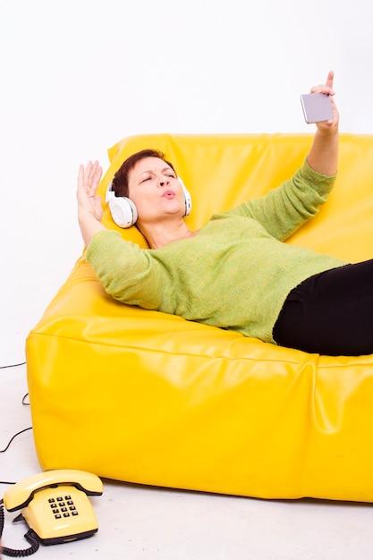 Mulher descansando no sofá e tirar selfies Foto gratuita