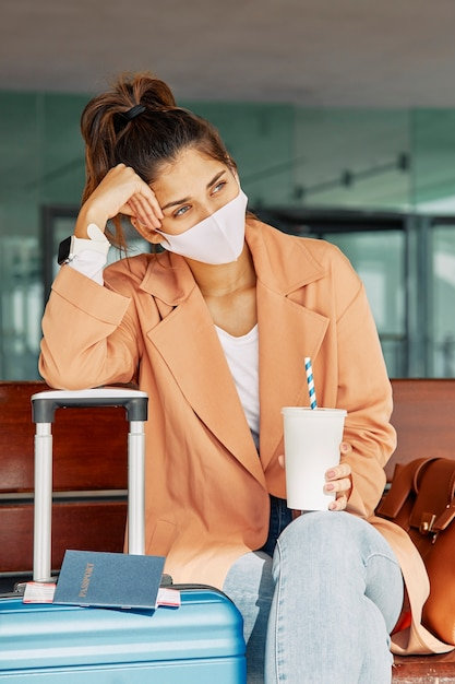 Mulher descansando sobre a bagagem enquanto usava máscara médica no aeroporto durante a pandemia Foto gratuita