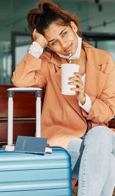Mulher descansando sobre a bagagem no aeroporto e tomando café durante a pandemia Foto gratuita