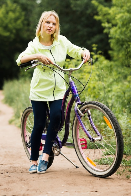Mulher, descansar, ligado, bicyle, ligado, floresta, estrada Foto gratuita