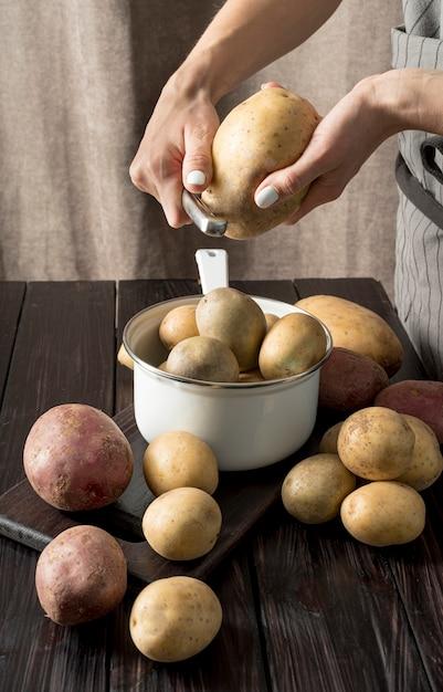 Mulher descascando algumas batatas cruas Foto gratuita