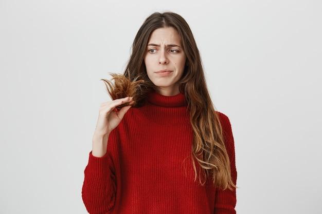 Mulher descontente olhando para pontas duplas do cabelo Foto gratuita