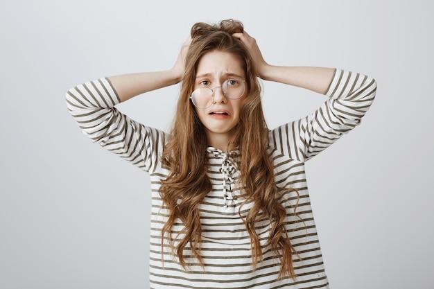 Mulher desesperada e chateada de óculos tortos em pânico, entrou em apuros Foto gratuita