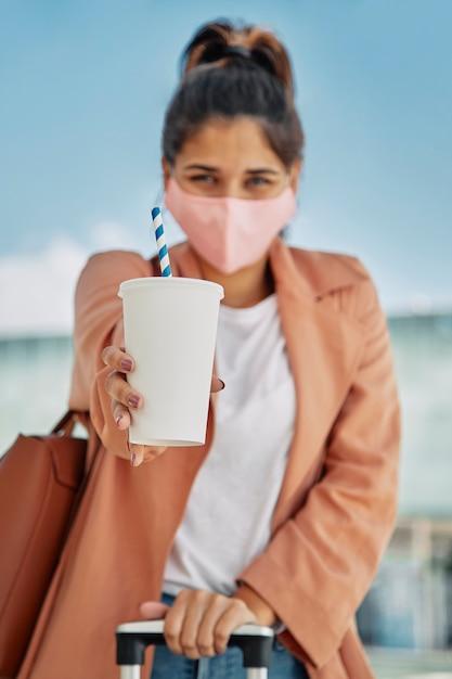 Mulher desfocada com máscara médica segurando bebida e bagagem no aeroporto durante a pandemia Foto gratuita