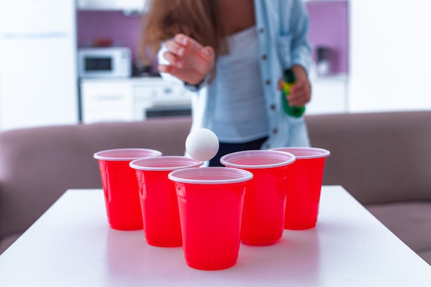 Mulher desfrutando de jogo de pong de cerveja na mesa em casa Foto Premium