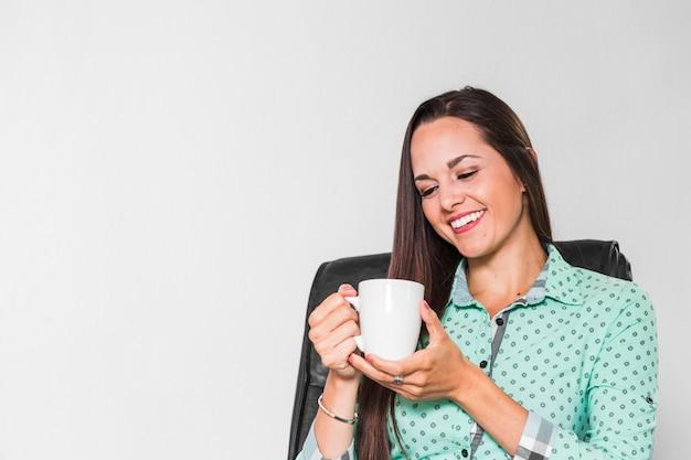Mulher, desfrutando, dela, xícara café, em, escritório Foto gratuita