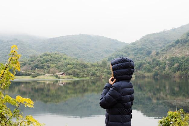 Mulher, desfrutando, paisagem, por, a, lago Foto gratuita