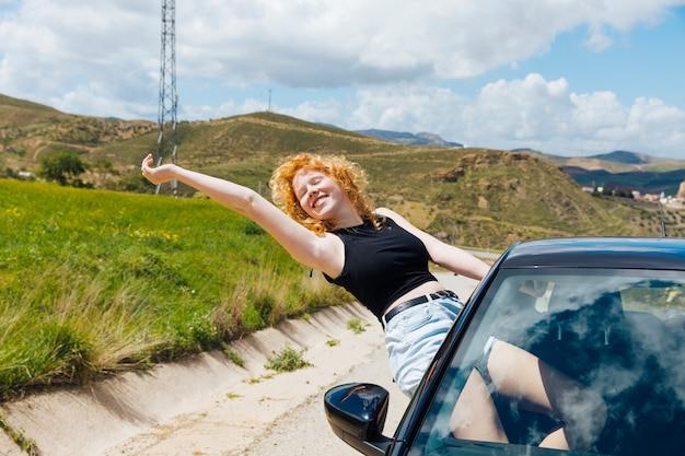 Mulher, desfrutando, viagem, saída, de, janela carro, e, esticar, braço, com, olhos fechados Foto gratuita
