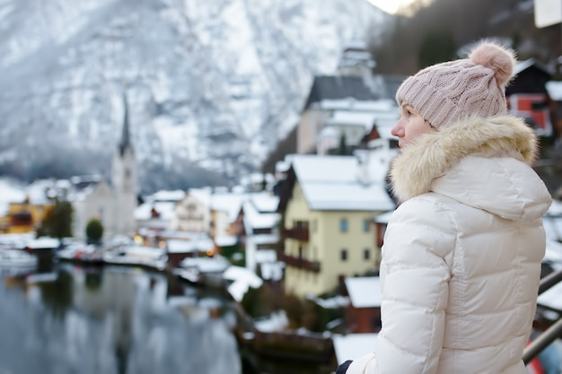 Mulher desfrutar de inverno vista panorâmica da vila de hallstatt, nos alpes austríacos Foto Premium