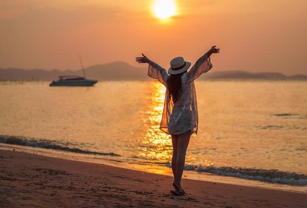 Mulher desfrutar na praia do mar com pôr do sol Foto Premium