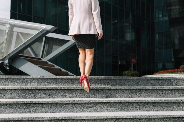 Mulher, desgastar, calcanhares altos, andar escada Foto gratuita