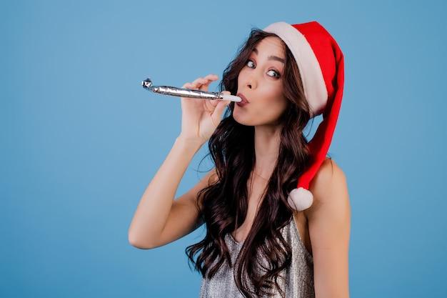 Mulher, desgastar, chapéu natal, soprar apito natal, isolado, sobre, azul Foto Premium