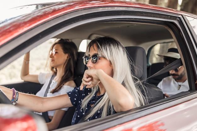 Mulher, desgastar, óculos de sol, dirigindo carro, com, dela, amigos Foto gratuita