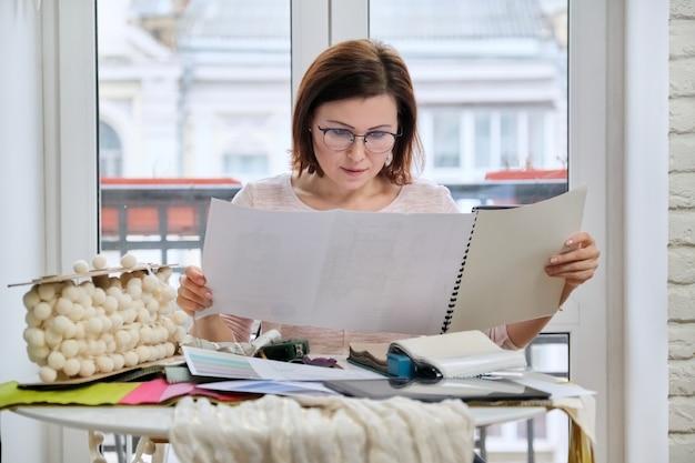 Mulher designer de interiores trabalhando à mesa de um escritório com amostras de tecidos decorativos de interiores para cortinas, estofados, acessórios Foto Premium
