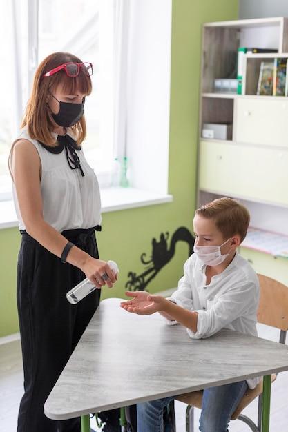 Mulher desinfetando as mãos de seu aluno Foto Premium