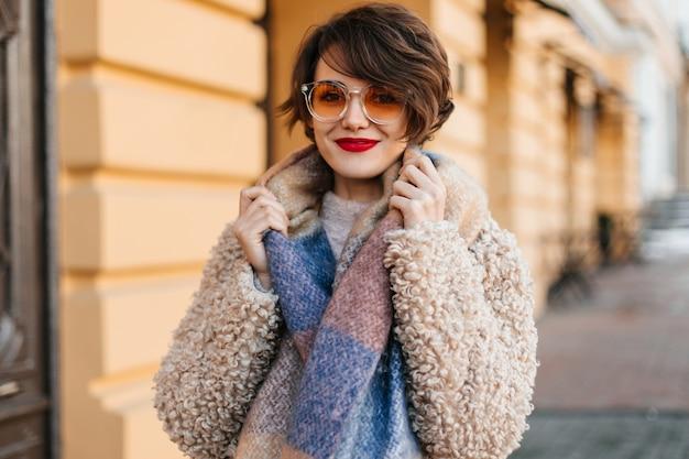 Mulher deslumbrante com lenço posando na rua Foto gratuita