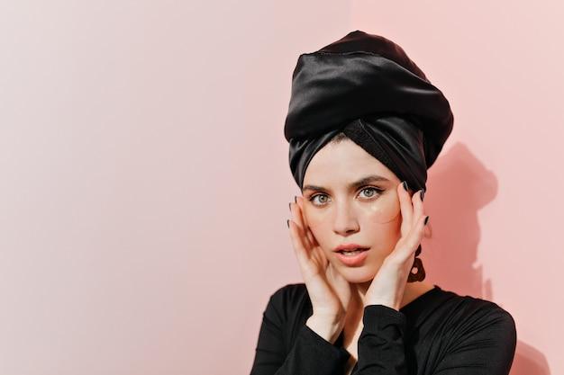 Mulher deslumbrante em roupas pretas fazendo rotina de cuidados com a pele Foto gratuita