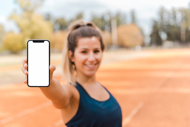 Mulher desportiva apresentando modelo de smartphone Foto gratuita