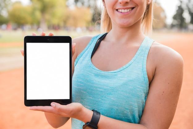 Mulher desportiva apresentando modelo de tablet Foto gratuita