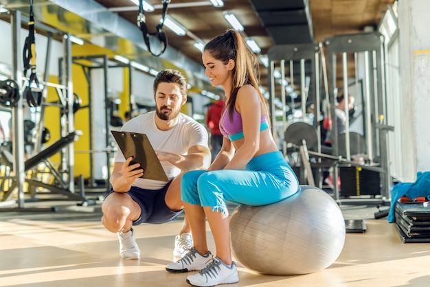Mulher desportiva caucasiana sorridente, sentado na bola de pilates e olhando os resultados do treinamento que seu personal trainer está mostrando a ela. trainer agachado ao lado dela. Foto Premium