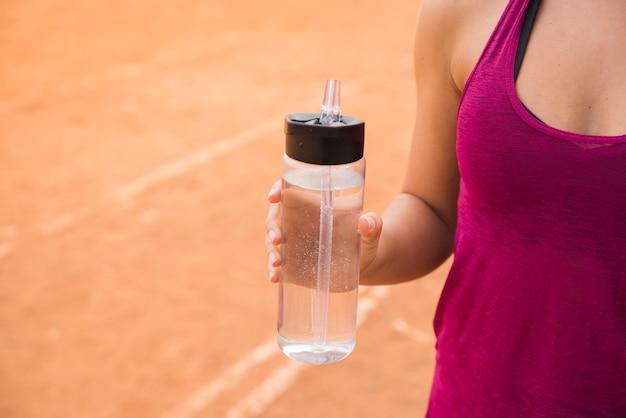 Mulher desportiva com garrafa de água na pista do estádio Foto gratuita