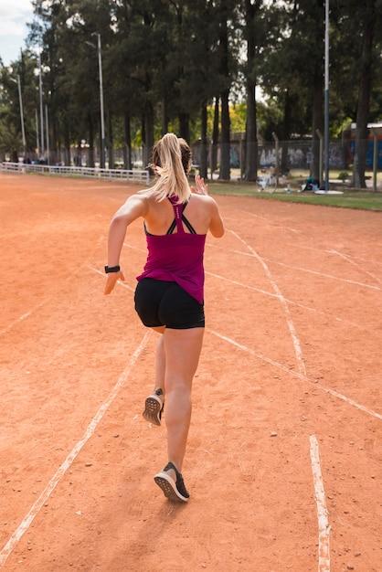 Mulher desportiva correndo na pista do estádio Foto gratuita