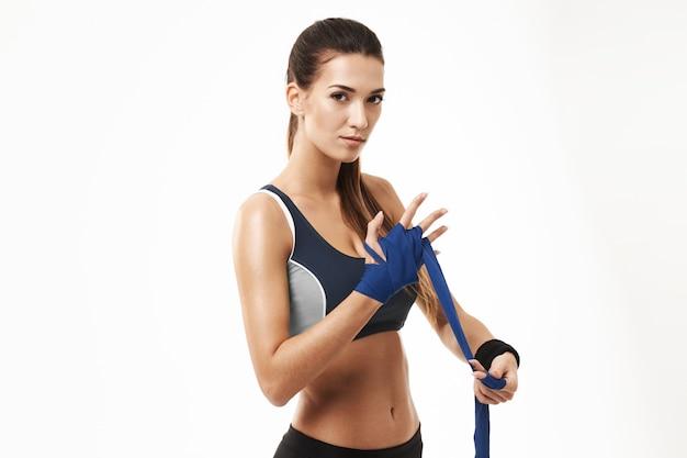 Mulher desportiva da aptidão que enrola a atadura elástica disponível no branco. Foto gratuita