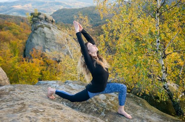Mulher desportiva do ajuste está praticando ioga no topo da montanha Foto Premium