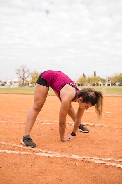 Mulher desportiva, estendendo-se na pista do estádio Foto gratuita