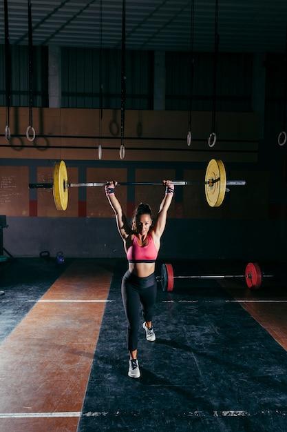 Mulher desportiva levantando a barra na academia Foto gratuita