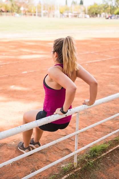 Mulher desportiva malhando na pista do estádio Foto gratuita