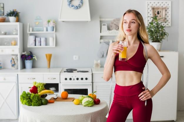 Mulher desportiva na cozinha com suco saudável Foto gratuita