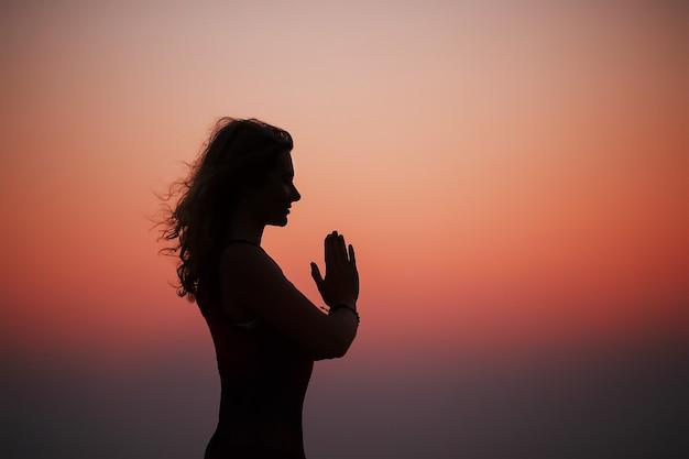 Mulher desportiva praticando ioga no parque ao pôr do sol Foto Premium