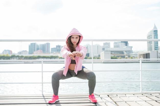 Mulher desportiva séria fazendo agachamentos em quay Foto gratuita