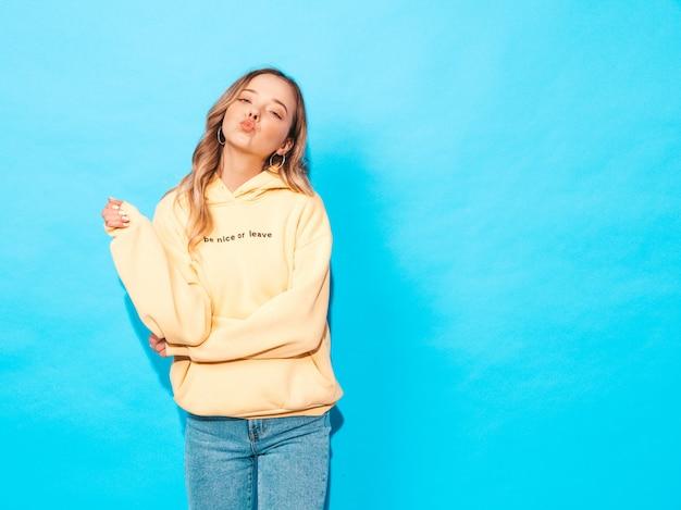 Mulher despreocupada posando perto da parede azul no estúdio Foto gratuita