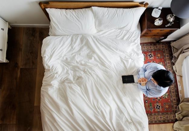 Mulher devota com um livro da bíblia rezando pela cama Foto gratuita