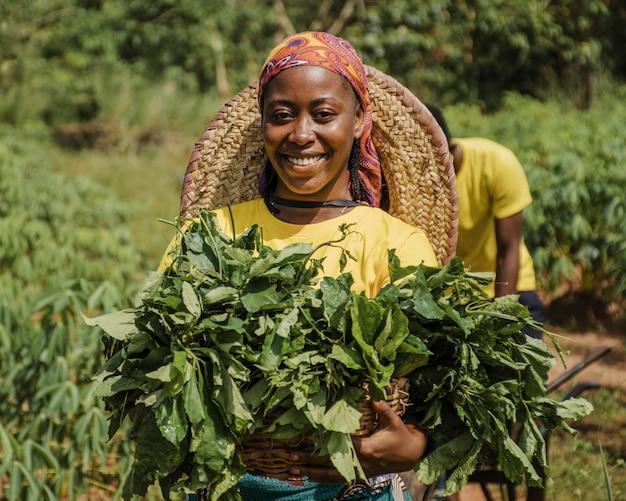 Mulher do campo segurando folhas de planta Foto gratuita