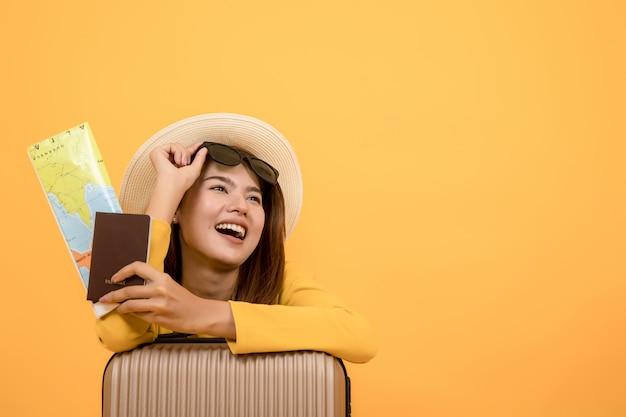 Mulher do turista do viajante na roupa ocasional do verão isolada sobre o fundo amarelo Foto Premium