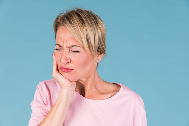 Mulher doente descontente tendo dor de dente e tocar sua bochecha Foto gratuita