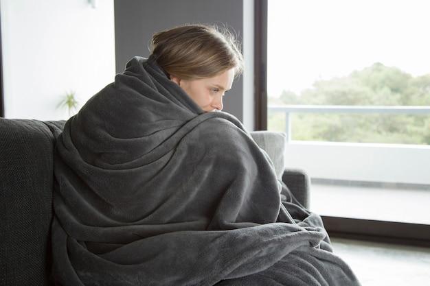 Mulher doente sentado no sofá, abraçando os joelhos, pensando Foto gratuita