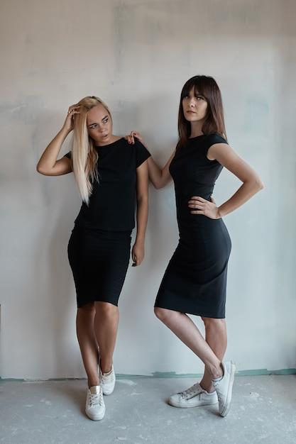 Mulher dois bonita em um vestido preto interno Foto gratuita