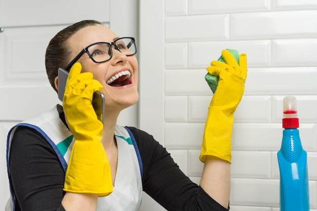Mulher dona de casa está limpando o banheiro e está sorrindo, falando ao telefone. Foto Premium