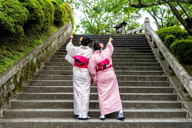 Mulher dos asiáticos que veste o quimono japonês no jardim. Foto Premium