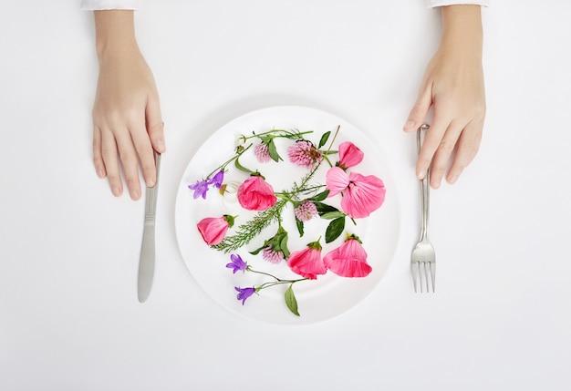 Mulher, e, bonito, primavera, flores, em, prato, mãos Foto Premium