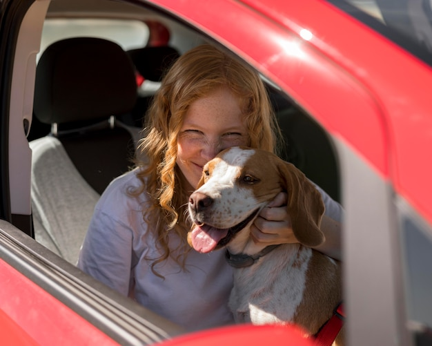 Mulher e cachorro feliz passeando de carro Foto gratuita